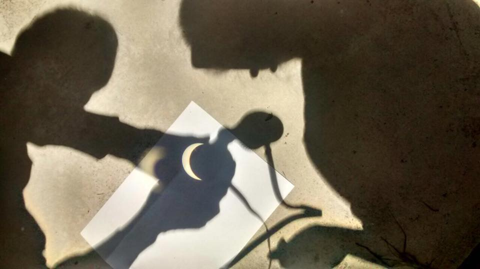 AOML Scientists use binoculars to reflect the sun onto the pavement. Image credit: NOAA