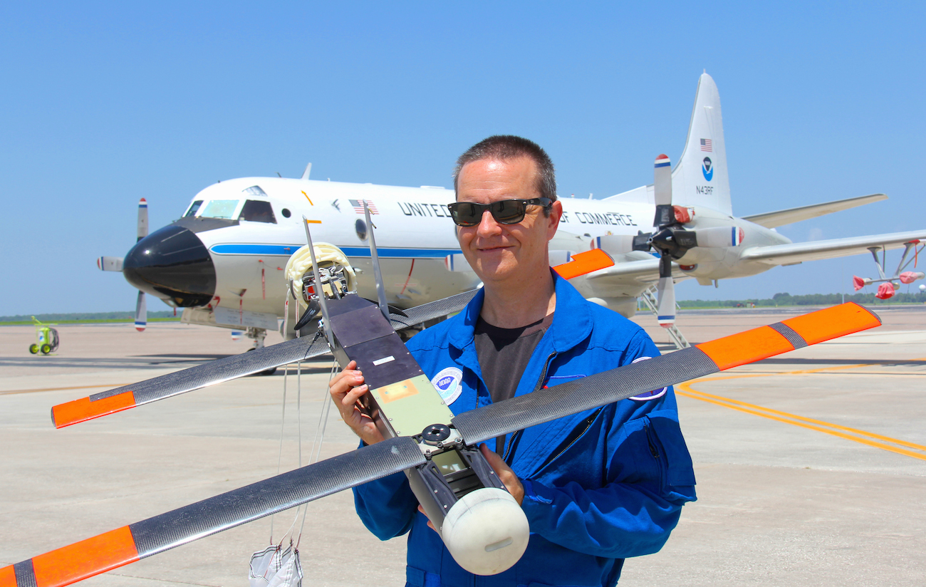 Dr. Joe Cione, hurricane researcher at NOAA's Atlantic Oceanographic and Meteorological Laboratory and chief scientist of the Coyote program, holds the Coyote in front of NOAA's P-3 aircraft. Image credit: NOAA