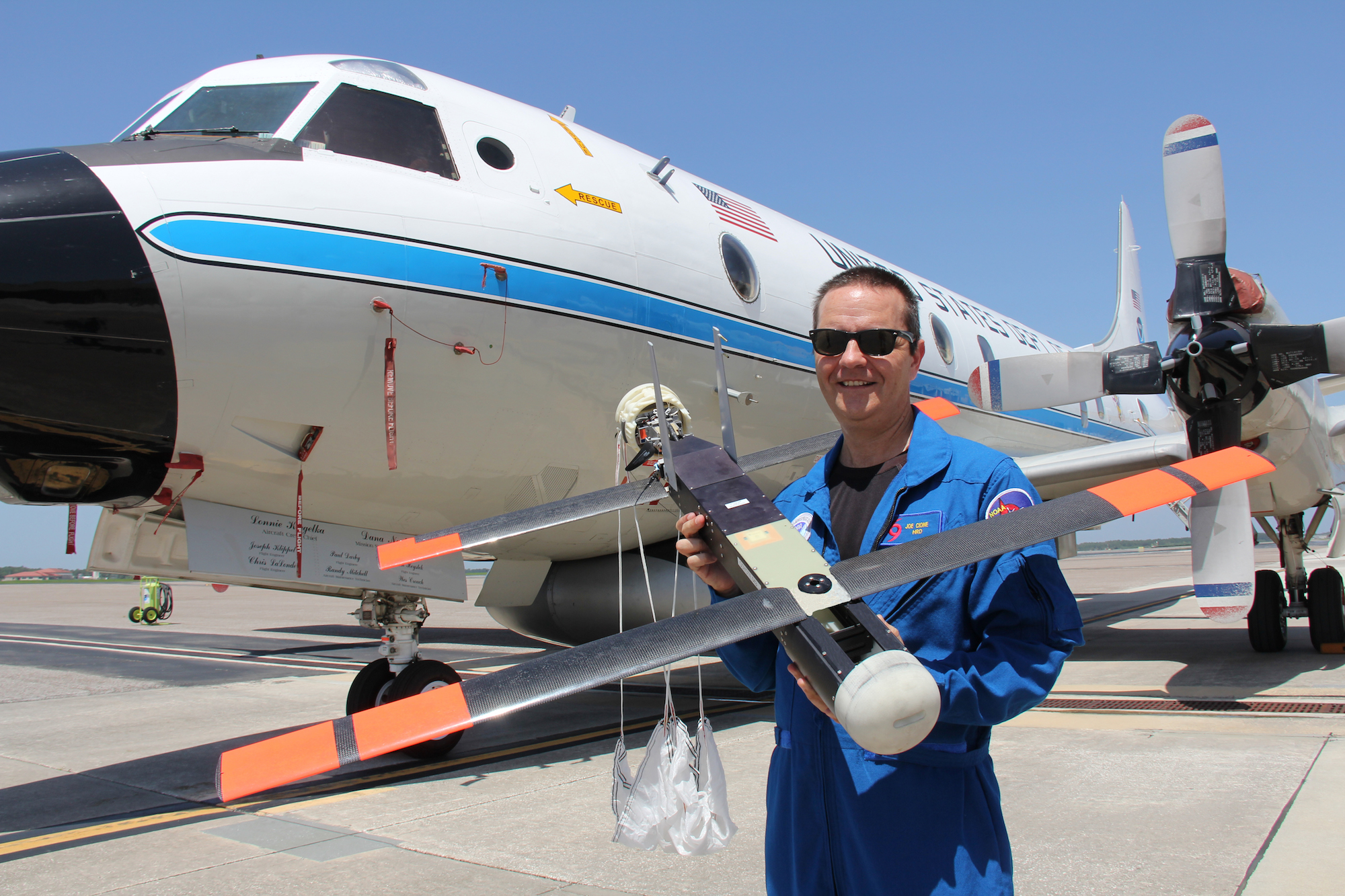 Dr. Joe Cione, hurricane researcher at NOAA's Atlantic Oceanographic and Meteorological Laboratory and chief scientist of the Coyote program, holds the Coyote in front of NOAA's P-3 aircraft at MacDill Air Force Base. Image credit: NOAA