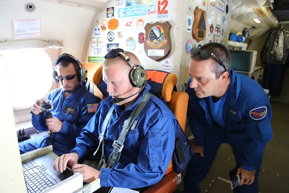 Drew Osbrink and Eric Redweik of Sensintel and NOAA's Dr. Joe Cione monitor data from the  Coyote after it was launched into  Hurricane Edouard. Image credit: NOAA