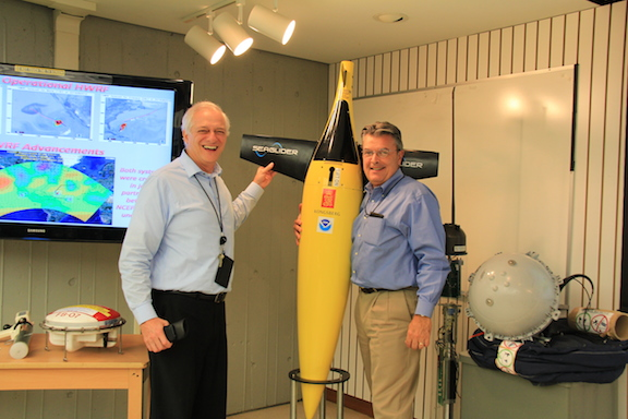 Dr. Gustavo Goni stops NOAA Deputy Assistant Administrator Craig McLean from taking the underwater glider display home with him. Image credit: NOAA