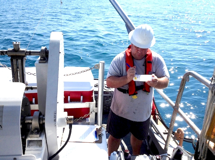 Charles Featherstone notating a sample bottle from a cast of the CTD instrument package off of Broward County. Image credit: NOAA