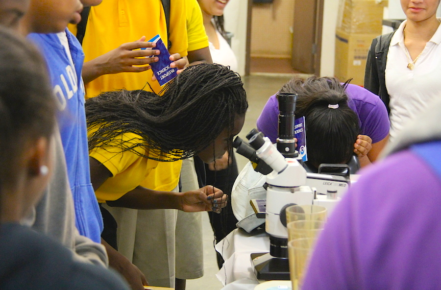 A pair of students observe microorganisms under the microscope. Image credit: NOAA