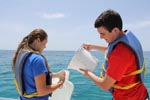 Two AOML interns work to collect a sample off the Florida Keys on Ocean Sampling Day 2014. Image credit: NOAA