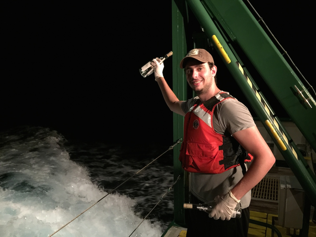 AOML Intern Ciro Liutti gets ready to release a message in a bottle off the back of the F.G. Walton Smith into the Florida Current. Image credit: NOAA