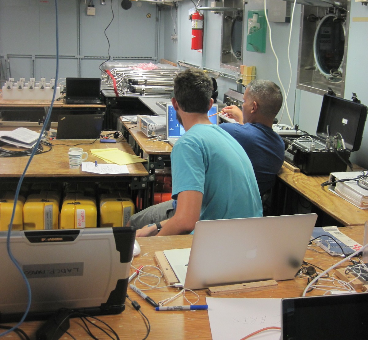 An AOML scientist (right) explains to one of the university students participating in the cruise how data is acoustically downloaded from one of the NOAA subsurface moored instruments. Image credit: NOAA