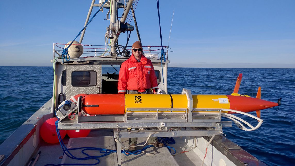 A NOAA Scientist stands next to an eAUV