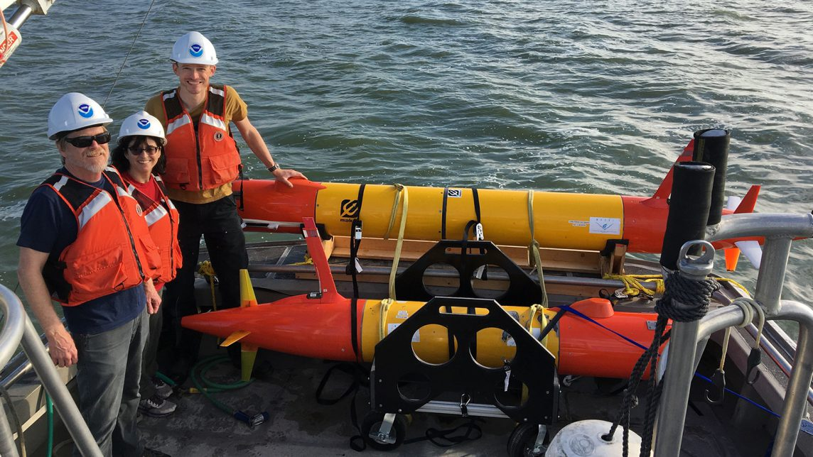 NOAA scientists stand next to an eAUV equipped with a 3rd Generation Environmental Sample Processor before deployment.