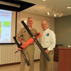Vice Admiral Devany and Dr. Spinrad pose with the Coyote Unmanned Aerial System. Image credit: NOAA