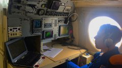 A hurricane researcher monitors storm conditions at a work station aboard the P-3 aircraft. Image credit: NOAA