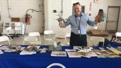 AOML Scientist Stan Goldenberg poses with instruments and models for teaching visitors about hurricane data collection. Image credit: NOAA
