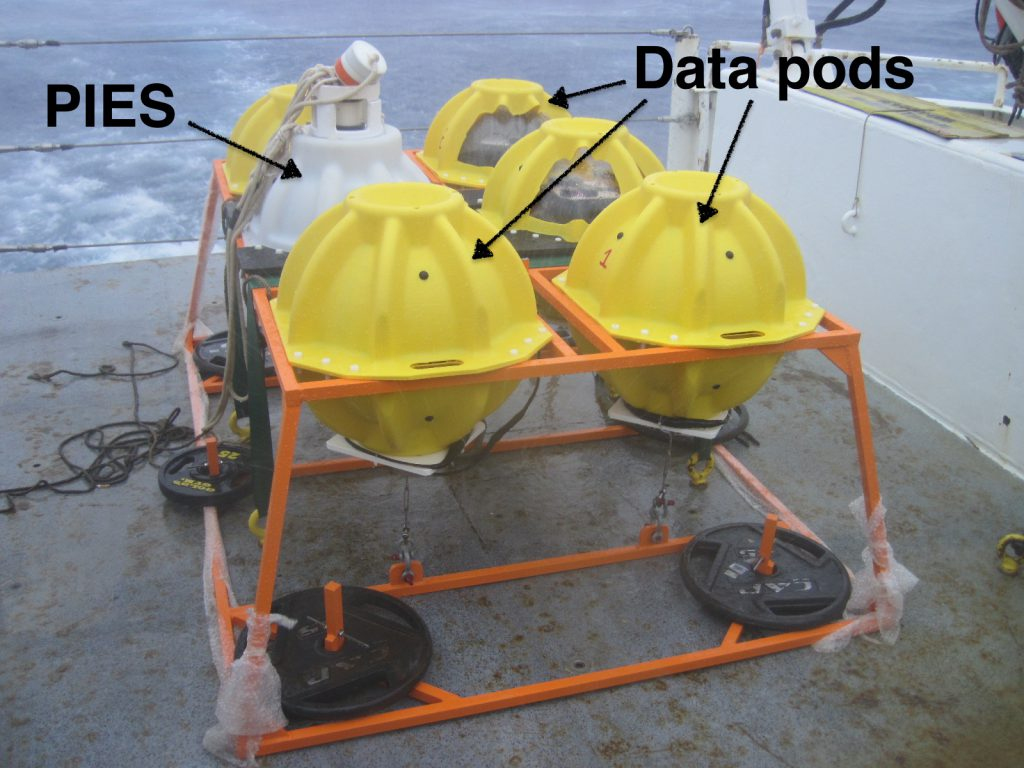 Photograph of a Pressure-equipped Inverted Echo Sounder (PIES) package additionally equipped with the AOML prototype ABIISS data pod retrieval system. The white sphere is a standard PIES instrument, while the yellow spheres are data pods. Photo Credit: NOAA
