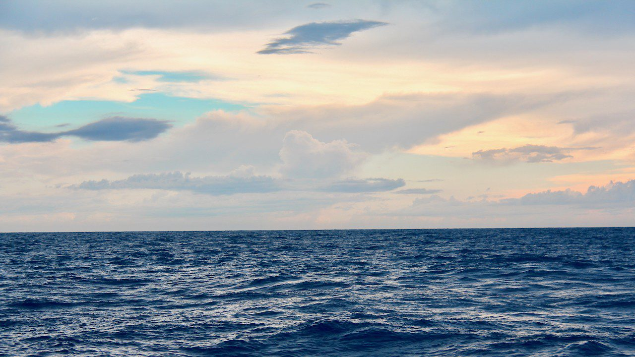 A photo shows a cloudy seascape and deep ocean waters. Photo Credit: NOAA AOML.